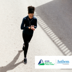 woman running and using a fitness tracker