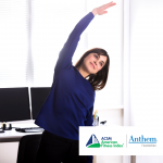 woman standing and stretching at her desk