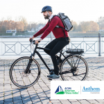man in red sweater riding a bike with a backpack