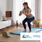 woman doing squats in living room in front of an open laptop